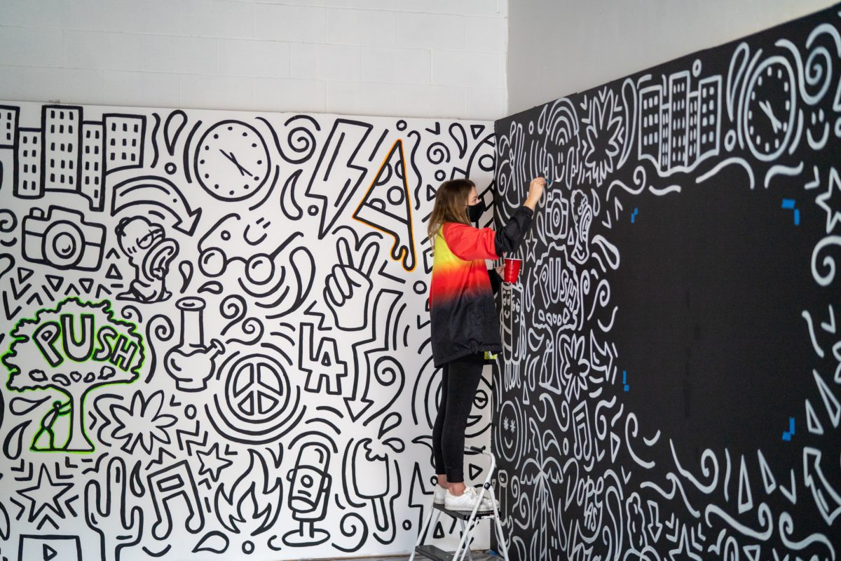 Woman standing on a ladder in a yellow and red shirt. She paints a black and white mural.