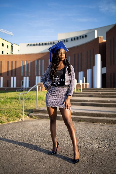"""Brianna stands outside of a school building wearing a tweed skirt and blazer, a """"black journalists matter"""" shirt, and a blue graduation cap."""