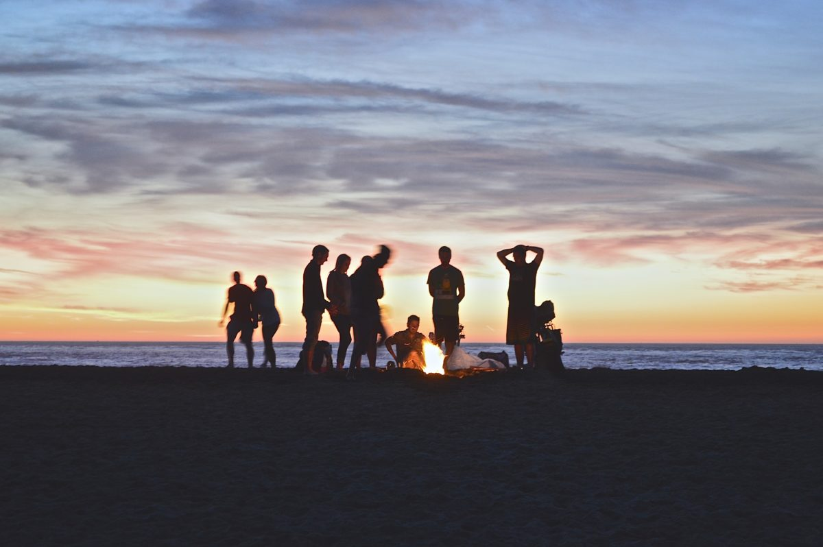 A group of people stand silhouetted against a sunset. Some stand while others sit by a bonfire. They are on a beach.