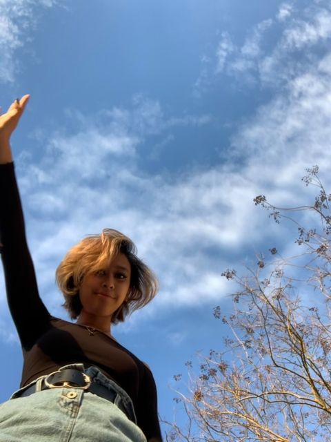 A girl with short brown hair looks down at the camera. Above her is a blue cloudy sky and behind her is a bare tree. She wears jeans, a black longsleeve shirt, and holds one arm up into the sky.