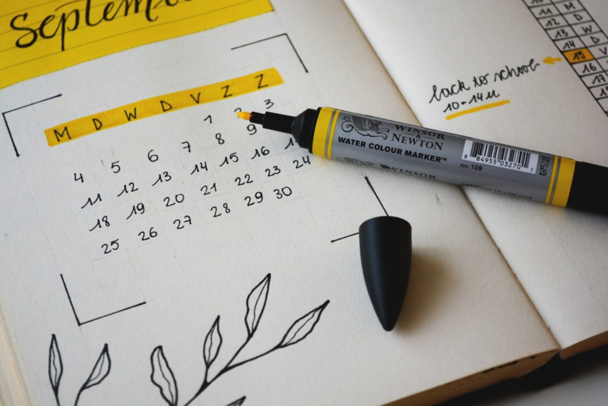 """A bullet journal spread. On the left page is the word """"September"""" written in cursive on a yellow sticky note. Below that is a small monthly calendar with the days of the week highlighted in yellow at the top. Below that is leaves drawn in black ink. On the right page is a series of numbers and letters, with a note that says """"back to school"""". On top of the journal is a yellow highlighter."""
