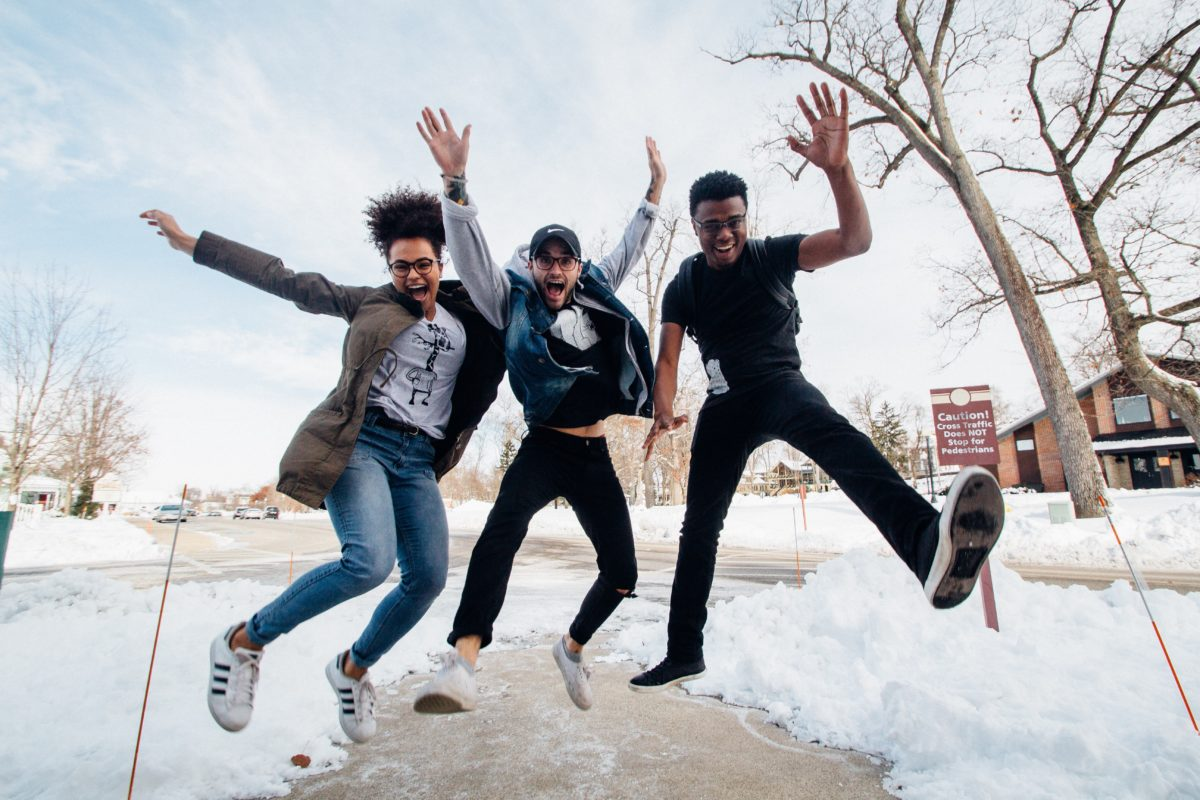 Three young adults jump in the air. Their legs and arms are out. On the ground is snow and behind them is a road, bare trees, and a brick building.