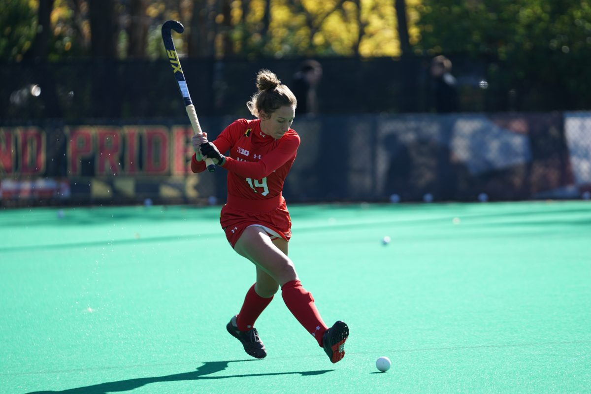 A girl in a red uniform plays field hockey on a field. She swings her stick behind her back and aims for a ball at her feet.