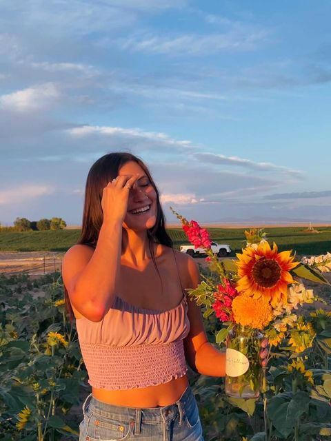 Emily, a young woman with light skin, stands outside in a field of sunflowers. She smiles widely and brushes her hair back with one hand while holding a sunflower in the other. She wears jeans and a pink tank top.