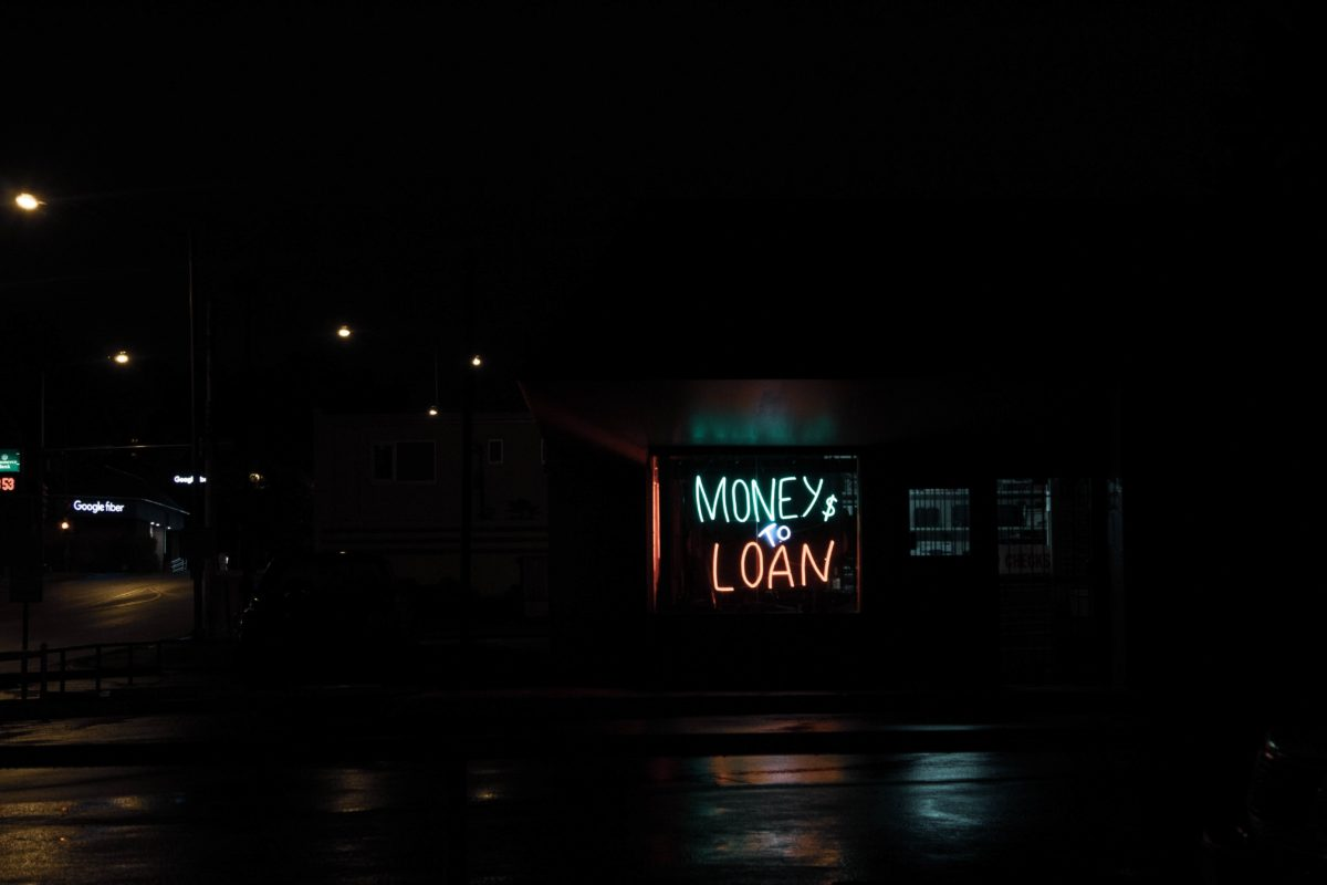 """A neon sign in the window of a building at night. It says """"Money $ To Loan"""""""
